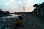 Power lines carry light and modern conveniences to the city, over the slums by the Indus River.